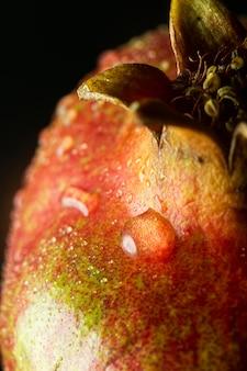 Fruta de granada de primer plano con gotas de agua