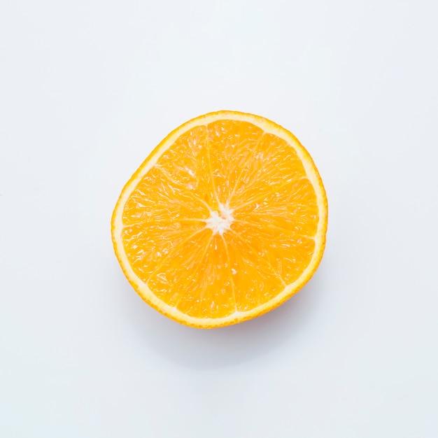 Fruta jugosa anaranjada partida en dos aislada en el fondo blanco