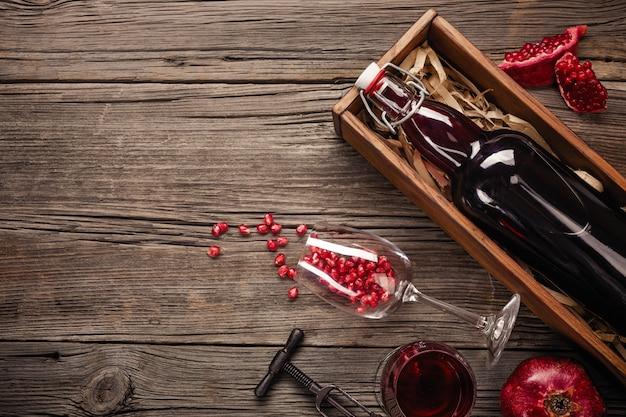 Fruta madura de granada con una copa de vino, una botella en una caja sobre un fondo de madera