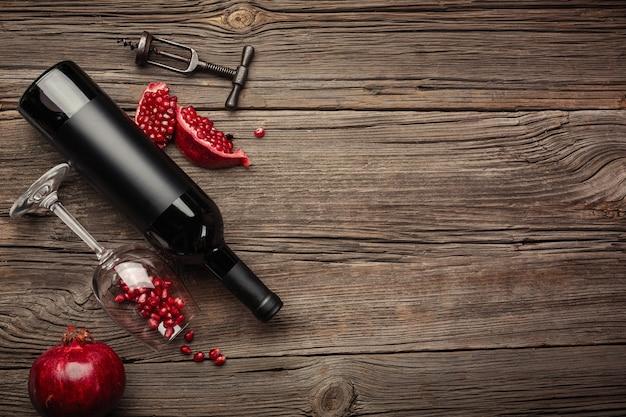 Fruta madura de granada con una copa de vino, una botella y un sacacorchos sobre un fondo de madera