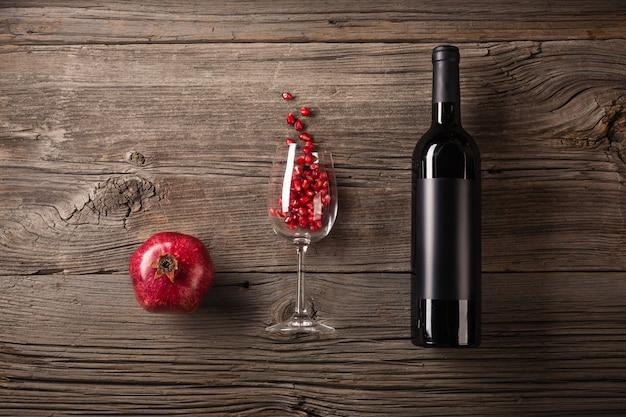 Fruta madura de granada con una copa de vino, una botella sobre un fondo de madera