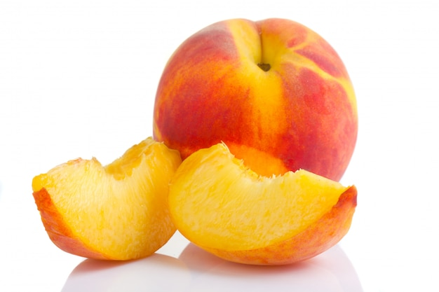 Fruta madura del melocotón con las rebanadas aisladas en blanco
