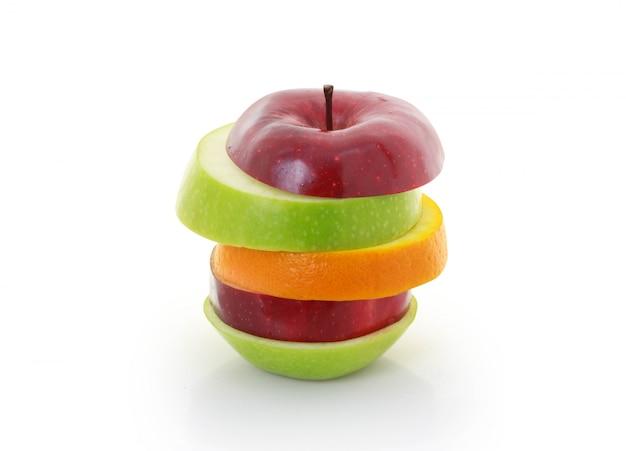 Fruta mixta en rodajas de manzana sobre fondo blanco.
