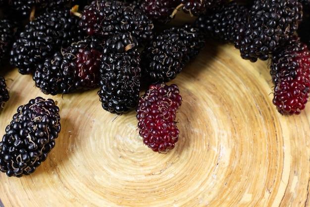 La fruta de la mora en el cuenco blanco en la tabla de madera.