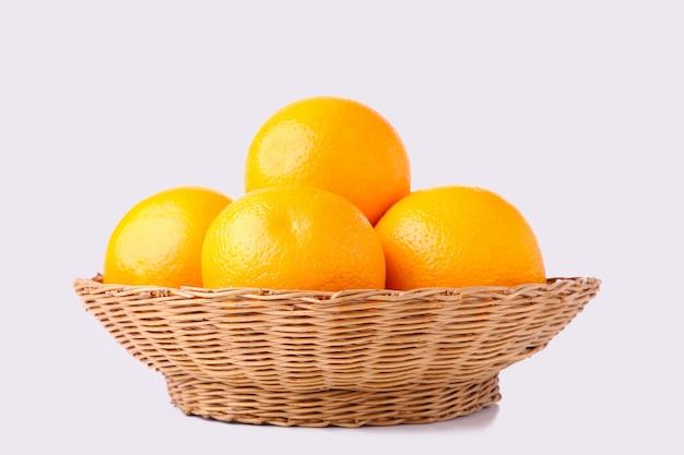 Fruta naranja en cesta sobre un fondo blanco.