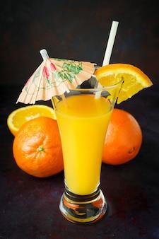 Fruta naranja natural oscura con paja y sombrilla.