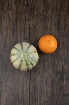 Fruta naranja sana entera con calabaza gris sobre mesa de madera.
