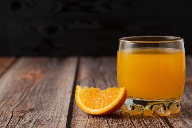 Fruta naranja con un vaso de jugo en la mesa de madera