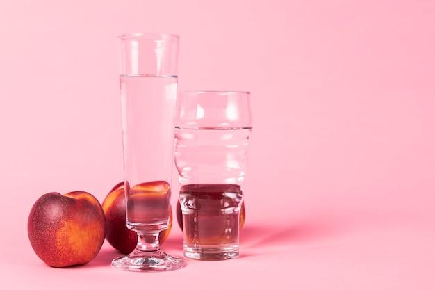 Fruta de nectarina y vasos de agua.
