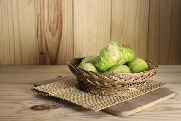 Fruta de noni en cesta de mimbre o morinda en cesta de mimbre en estera de bambú en mesa de madera