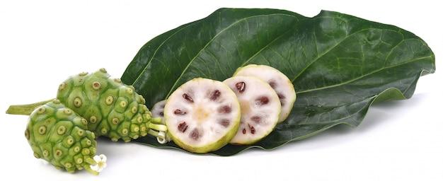 Fruta de noni con hoja verde sobre fondo blanco