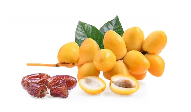 Fruta de la palmera datilera fresca y seca sobre superficie blanca