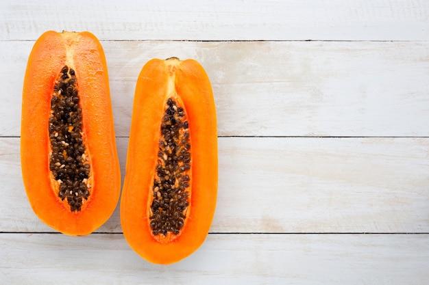 Fruta de la papaya en el escritorio de madera blanco con el espacio de la copia, visión superior.