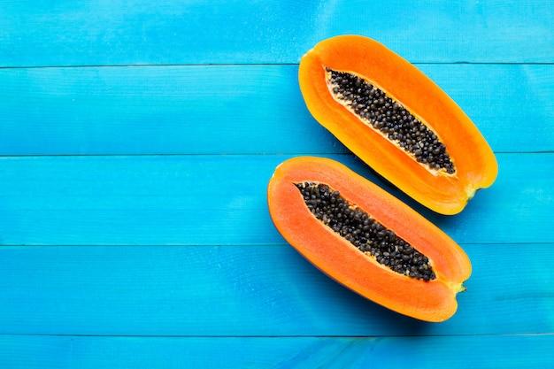 Fruta de la papaya en el fondo de madera azul