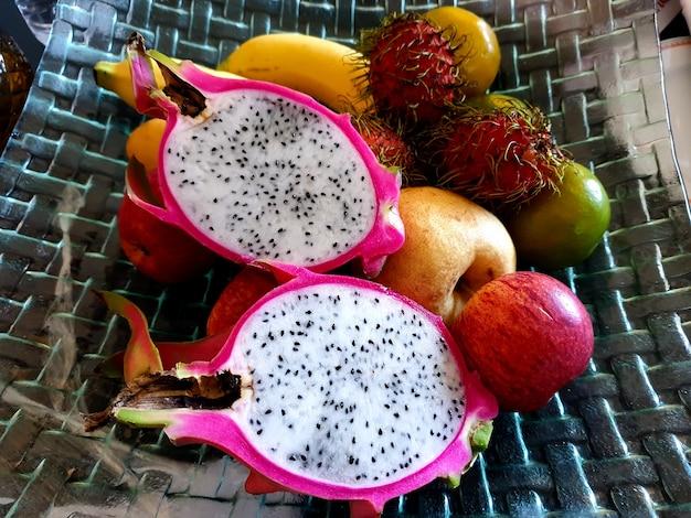 Fruta en el plato moderno como fruta del dragón, plátano, manzana, rambután, pera china