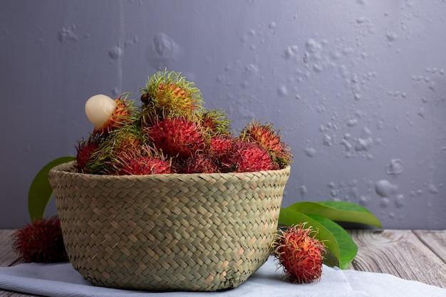 Fruta del rambután en cesta en la tabla de cocina, fruta dulce tailandesa.