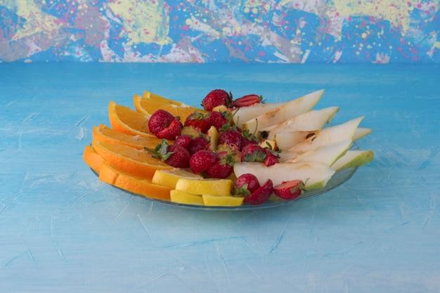 Fruta en rodajas en un plato de vidrio aislado en el espacio azul