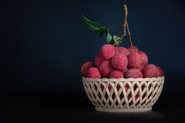 Fruta roja del lichi colocada en una cesta.