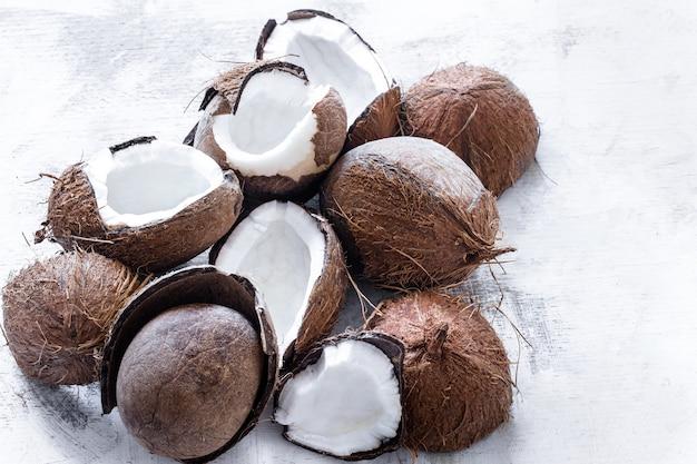 Fruta tropical de coco rozbitogo reducido a la mitad sobre un fondo claro, el concepto de fruta orgánica