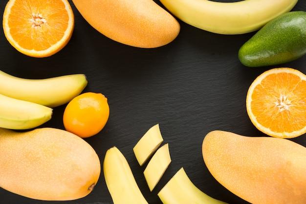 Fruta tropical fresca, mango, plátano, naranja, limón, aguacate alrededor en un plato de pizarra.