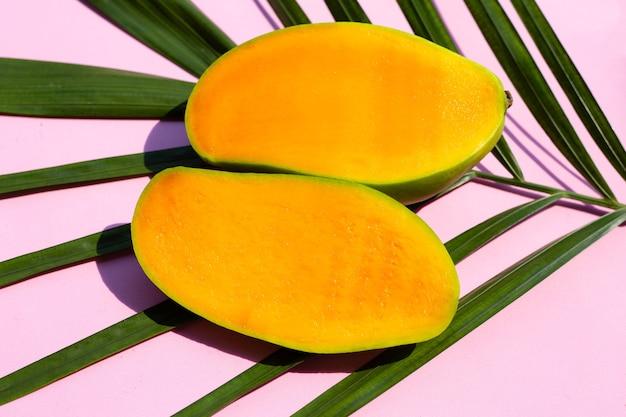 Fruta tropical, mango con hojas verdes sobre superficie rosa