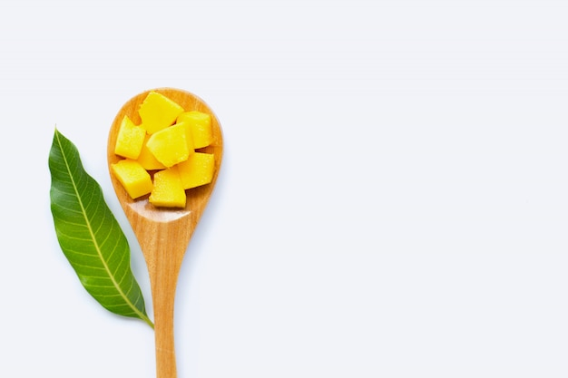 Fruta tropical, rodajas de cubo de mango y hoja con cuchara de madera sobre fondo blanco.