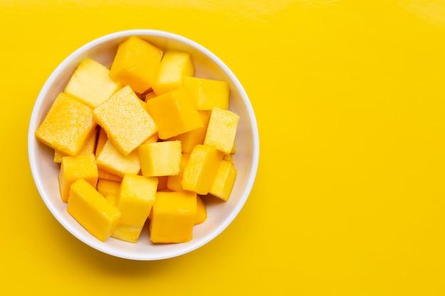 Fruta tropical, rodajas de cubo de mango en un tazón blanco