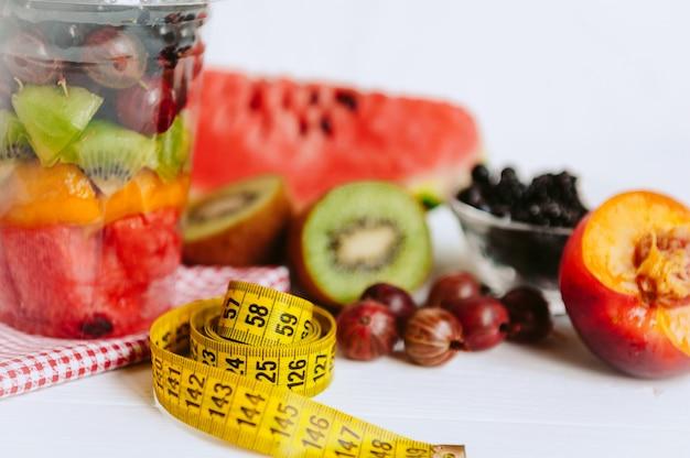 Fruta en un vaso y una cinta para medir el cuerpo.