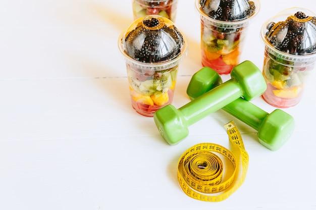 Fruta en un vaso, una mancuerna y una cinta para medir el cuerpo. concepto de nutrición saludable y pérdida de peso.