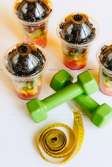 Fruta en un vaso, pesas y una cinta para medir el cuerpo.