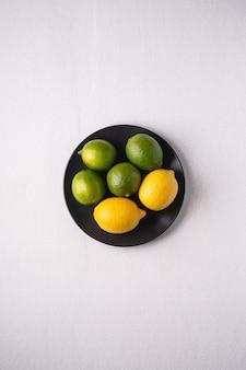 Frutas agrias de lima y limón en placa negra sobre blanco