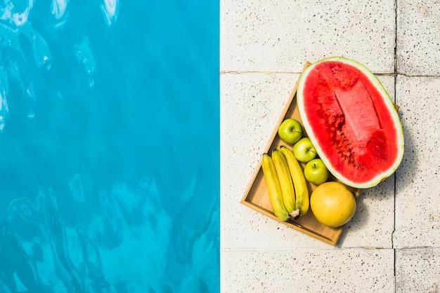 Frutas en bandeja colocadas en borde de piscina.