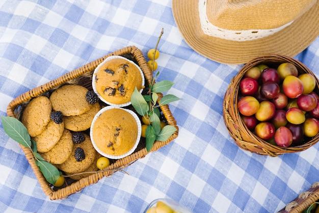 Frutas y bayas en cestas de picnic sobre un mantel a cuadros blanco azul sobre un césped verde y un sombrero de paja
