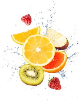 Frutas, bayas y un chorrito de agua sobre un fondo blanco.