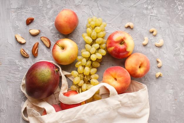 Frutas en bolsa blanca textil de algodón reutilizable sobre un fondo de hormigón gris cero residuos compras concepto de almacenamiento y reciclaje plano lay