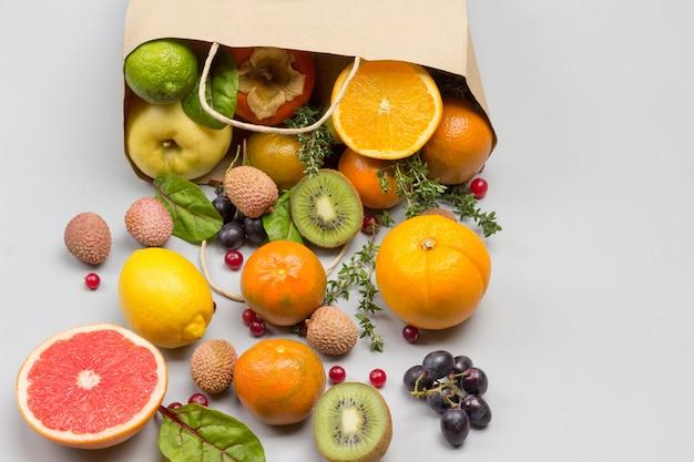 Frutas en bolsa de papel. caqui, kiwi y naranja en mesa