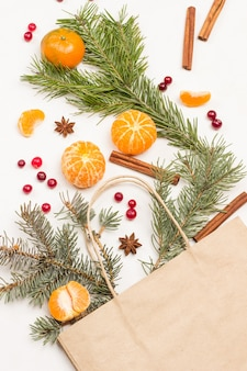 Frutas en bolsa de papel. mandarinas enteras, gajos de mandarina pelados. arándanos y especias, ramitas de abeto en la mesa. endecha plana