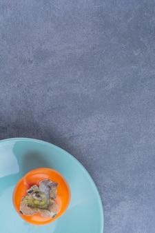 Frutas de caqui en una mesa de mármol plateon.