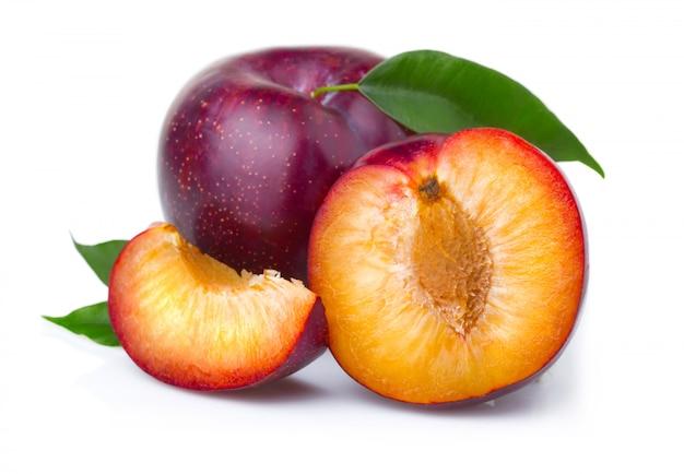 Frutas de ciruelo moradas maduras con hojas verdes aisladas