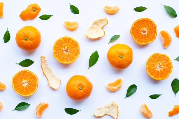 Frutas cítricas anaranjadas frescas con cáscara y hojas verdes en blanco