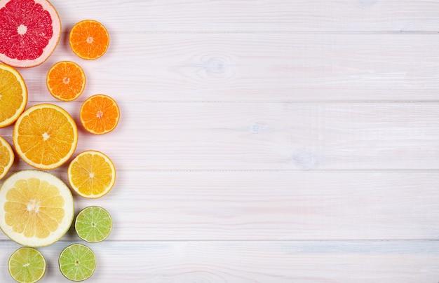 Frutas cítricas de colores sobre fondo blanco de madera
