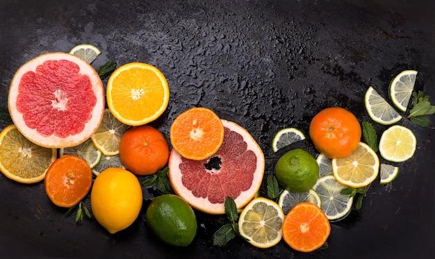 Frutas cítricas frescas: limones, naranjas, limas, pomelos sobre superficie negra