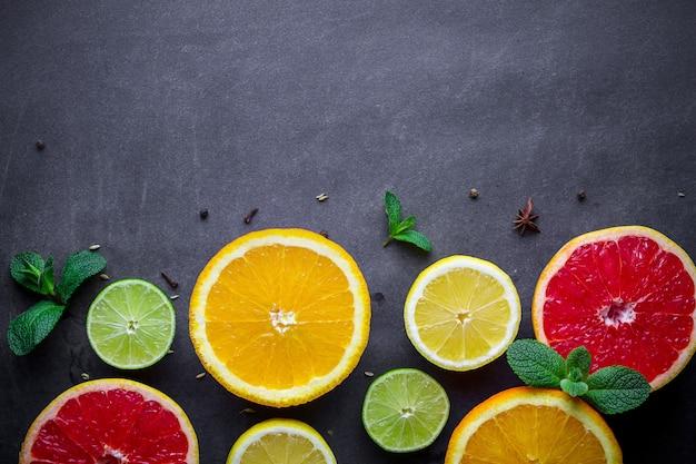 Frutas cítricas frescas y maduras y hojas de menta verde sobre fondo oscuro