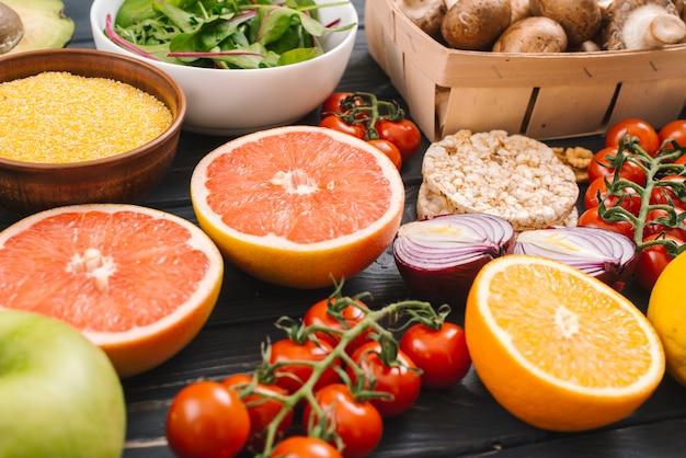Frutas cítricas frescas; pastel de arroz inflado en mesa de madera y verduras.