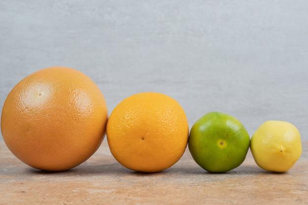 Frutas cítricas frescas sobre fondo de mármol.