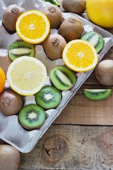 Frutas cítricas jugosas frescas en una bandeja de caja en madera