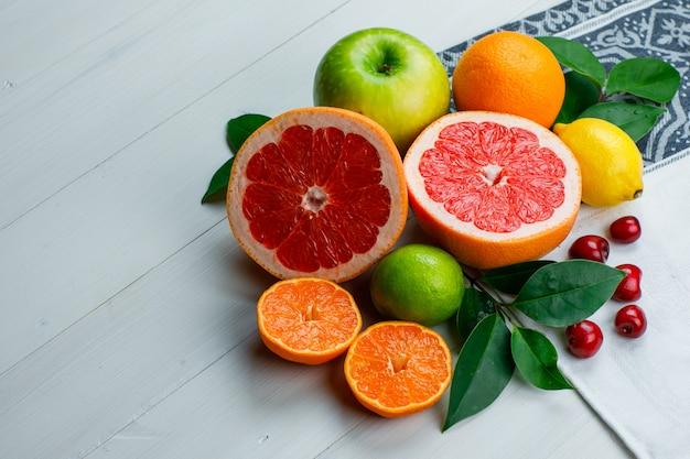Frutas cítricas con manzana, cerezas, hojas de alto ángulo de vista en la mesa de madera y paño de cocina
