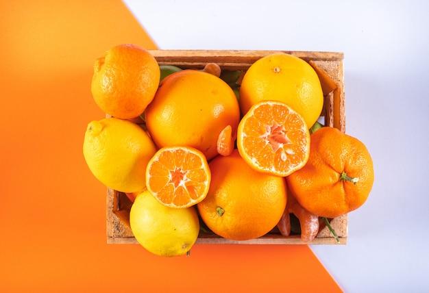 Frutas cítricas de naranja fruta de mandarina en caja de madera sobre superficie mixta de naranja y blanco