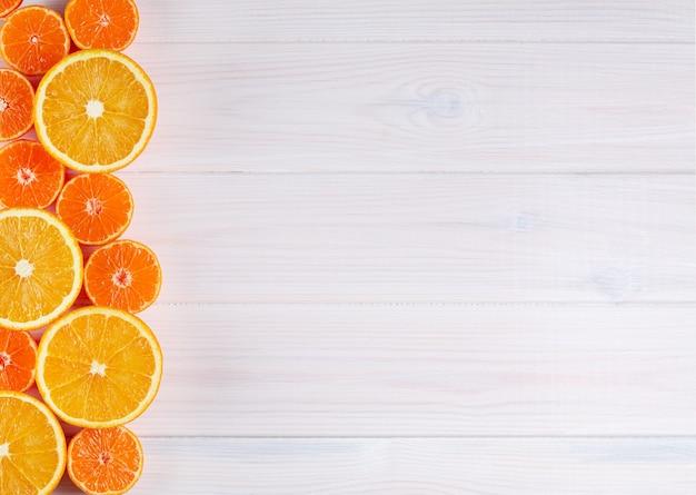 Frutas cítricas naranjas sobre fondo blanco de madera