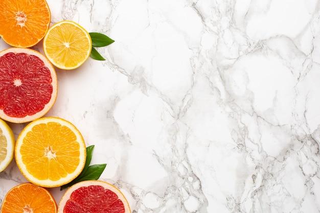 Frutas cítricas en superficie de mármol con copyspace, fruta flatlay, composición mínima de verano con pomelo, limón, mandarina y naranja